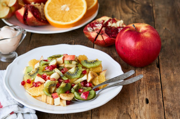 Salad with various fresh fruits on a white plate