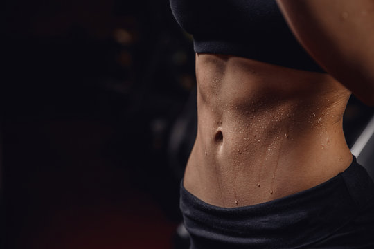 Inflated body fitness of young woman, abdominal muscles dices. Concept sweat after exercise