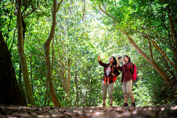 Two young Asian female hipster hiking in forest
