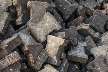 Pile of old discarded pavement (segmental paver) cobble stones.