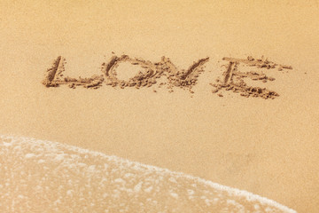 Word LOVE written in wet sand on the beach, sun shining over.