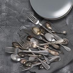 Vintage silverware and plates on dark grey
