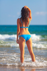 Pretty woman in blue bikini posing on a sea beach