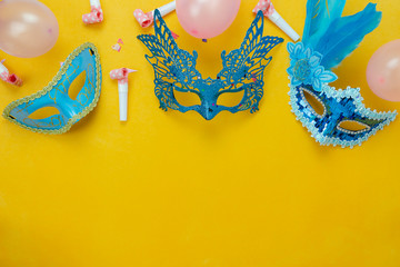 Table top view aerial image of beautiful colorful carnival season or photo booth prop Mardi Gras background.Flat lay object blue mask with decorations and confetti & pink balloon on yellow wallpaper.