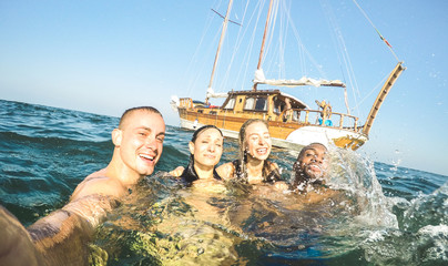 Young millennial friends taking selfie and swimming at sailing boat sea trip - Rich guys and girls having fun in summer party day - Exclusive vacation concept - Bright sunny afternoon filter