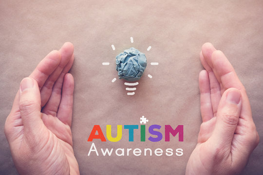 Blue paper light bulb and puzzle with hands, world Autism awareness day