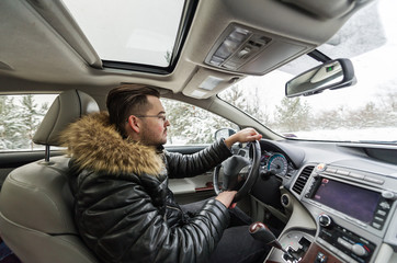 Handsome young man driving in car through winter forest