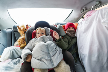 Two children in warm clothes is in the car in wintertime.