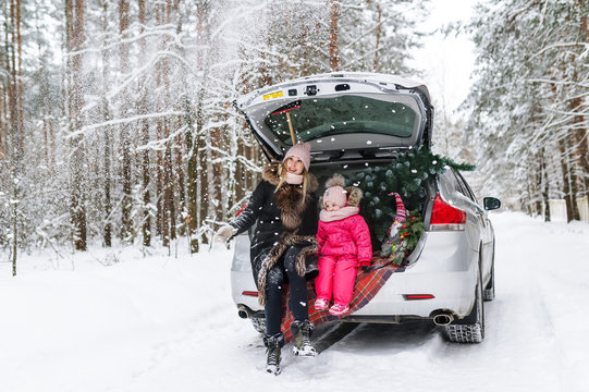 Happy mother with the little daughter and Christmas tree sitting in the car in the winter forest