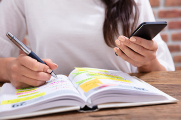 Fototapete - Businesswoman Holding Cellphone Writing Schedule In Diary