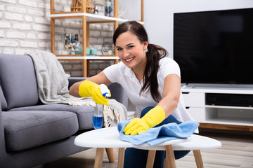 Female Janitor Cleaning Table With Blue Rag
