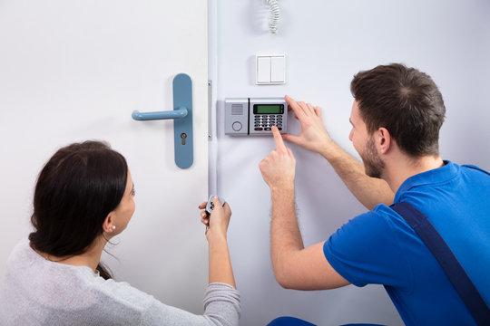 Handyman Installing Security System Near Door Wall