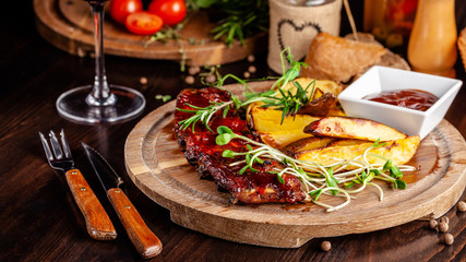 Grilled ribs with potatoes in a rustic style with barbecue sauce. Serving dishes in the restaurant on a wooden board. A glass of cool wine. Background image close up. copy space