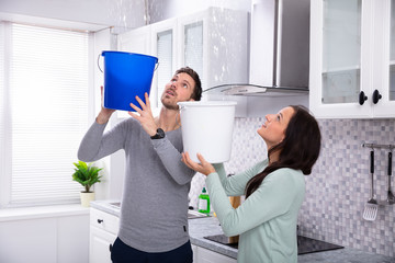Couple Collecting Water Leaking From Ceiling In Bucket