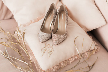Blush pink bridal shoes and accenting jewelry with gold floral decoration. Pink background. Close up and top view.