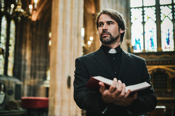 Christian priest standing by the altar
