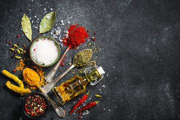 Spices and olive oil on black stone background.