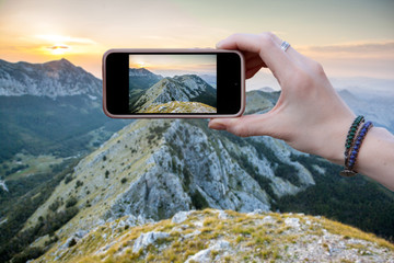 Woman tourist photographs on smartphone beautiful view of the mountain range in Montenegro. Travel concepts and technology. close up