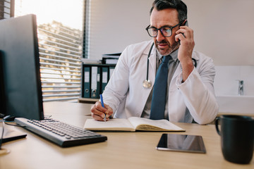 Doctor talking on phone and making notes