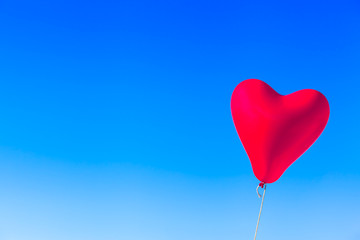 Flight with Love / Flying heart shaped red balloon tied by rope at blue sky background (copy space)
