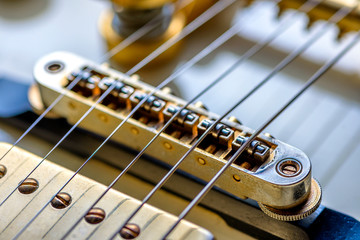 A very close view of an electric rock guitar body, strings and pickups