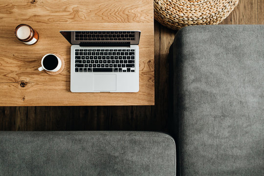 Top view of laptop, coffee cup and candle on wooden table. Blogger / freelancer home office workspace flatlay. Modern nordic interior design concept.