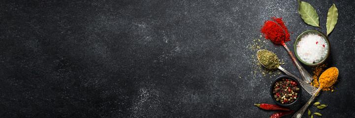 Fototapeta Spices, sea salt and pepper on black stone background. obraz