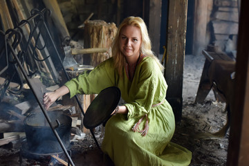 girl in vintage viking clothing prepares food in a cauldron on a fire