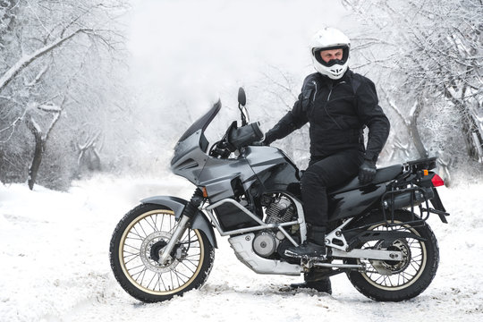 Rider man on adventure motorcycle. Winter fun. snowy day. the snow under the wheels of a motorbike. Enduro. off road dual sport travel tour, active life style concept. winter clothes, equipment