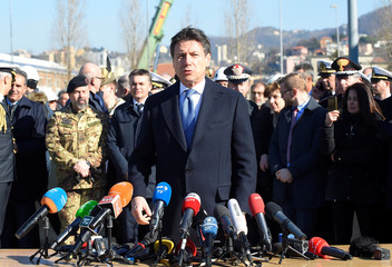 Italy's Prime Minister Giuseppe Conte speaks to the media as he visits the collapsed Morandi Bridge in Genoa