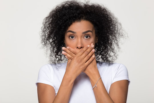 Shocked scared african woman with surprised face covering mouth
