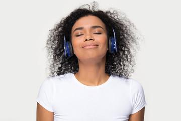 Happy calm african teen girl wearing headphones listening to music