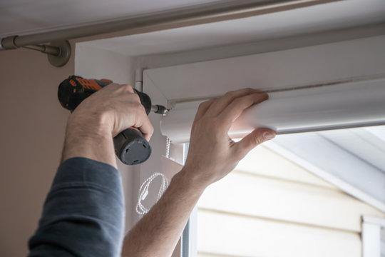 worker mounts roller blinds on window frames