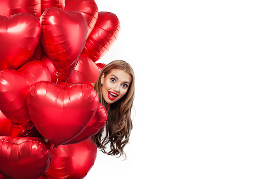 Excited young woman with balloons red heart isolated on white background. Surprised girl. Surprise, valentines people and Valentine's day concept
