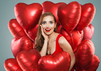 Young pretty woman holds red balloons. Surprised model girl with red lips makeup, perfect curly hairstyle and cute smile. Gifts, birthday and Valentine's day concept