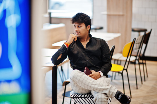 Stylish indian man sitting at fast food cafe and waiting his order.