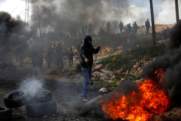 Palestinian demonstrator moves a tire during clashes with Israeli troops near Nablus in the Israeli-occupied West Bank
