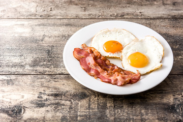 Fried eggs and bacon for breakfast on wooden table. Copyspace