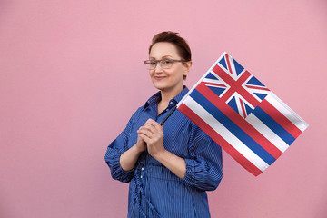 Hawaii flag. Woman holding Hawaii state flag. Nice portrait of middle aged lady 40 50 years old holding a large state flag over pink wall background on the street outdoor.