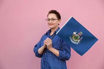Maine flag. Woman holding Maine state flag. Nice portrait of middle aged lady 40 50 years old holding a large state flag over pink wall background on the street outdoor.