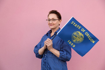Oregon flag. Woman holding Oregon state flag. Nice portrait of middle aged lady 40 50 years old holding a large state flag over pink wall background on the street outdoor.