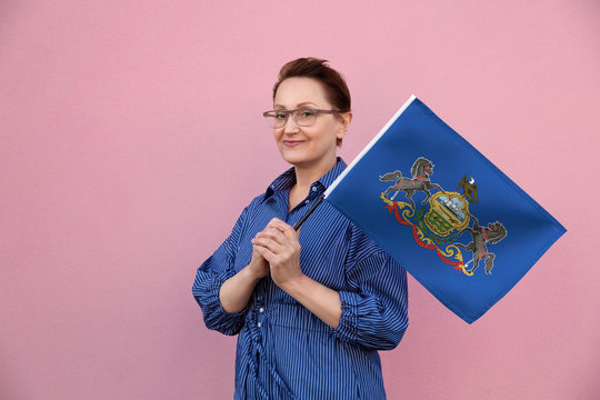 Pennsylvania flag. Woman holding Pennsylvania state flag. Nice portrait of middle aged lady 40 50 years old holding a large state flag over pink wall background on the street outdoor.