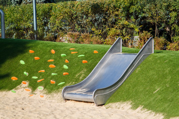 modern playground with a metal slide inscribed in the landscape design with a ladder of plastic shells made on the hillside