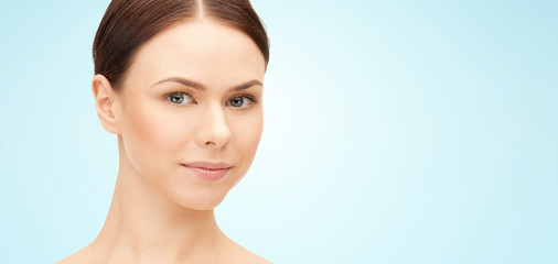 beauty and people concept - face of beautiful young woman over blue background