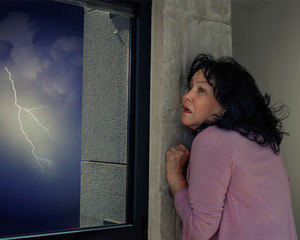 Middle-aged woman is afraid of thunderstorms