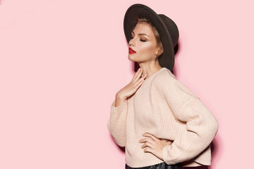 Wall Mural - Portrait of attractive well-dressed model in comfy beige sweater and stylish black hat. Modern vogue fashion and autumn concept. Copy space in left side