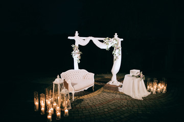 Arch with fresh flowers for a wedding ceremony  at night