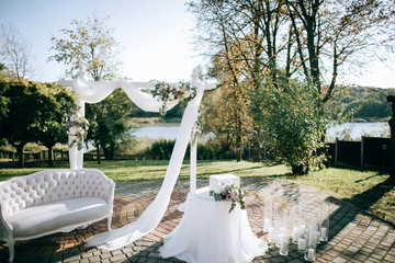 Beautiful wedding ceremony on the shore of the lake and arch with fresh flowers
