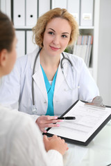 Happy blonde female doctor and patient discussing medical examination results. Medicine, healthcare and help concept