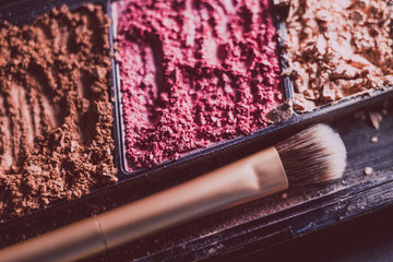 crushed blush and bronzer powders with brush, close-up shot